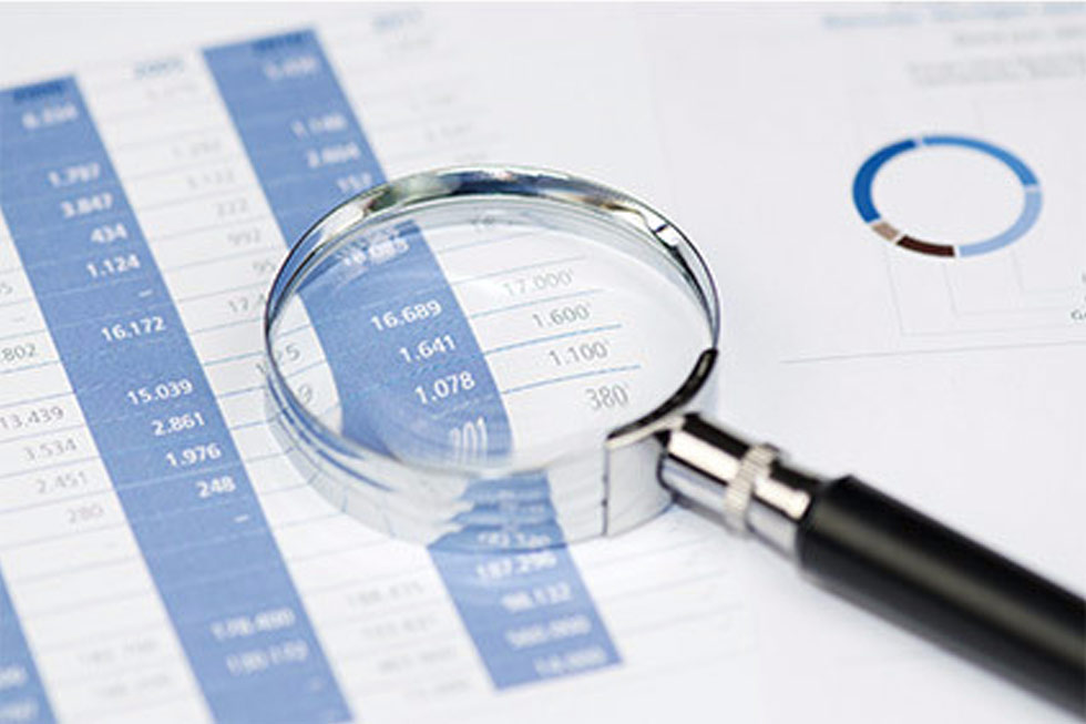 Magnifying glass being used to view financial report